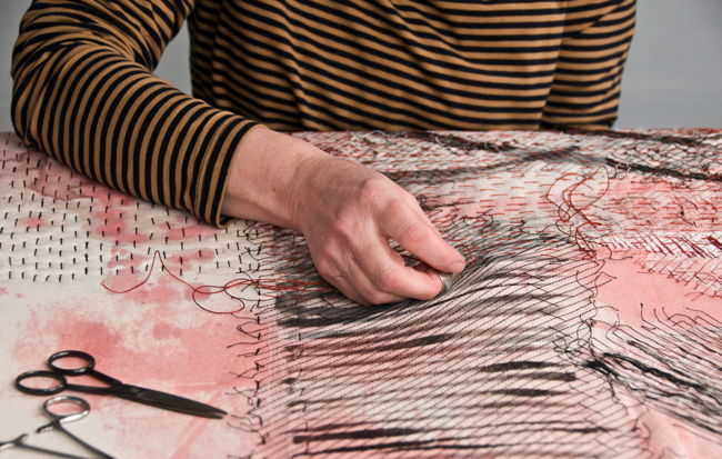Pauline Burbidge hand stitching her quilt Lindisfarne Revisited